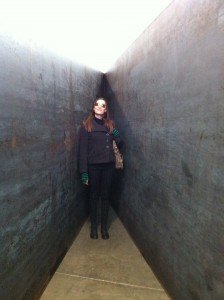 Me standing in a Richard Serra sculpture at Gagosian Gallery, New York City, October 2013. I'm wearing sunglasses, grey short coat, fingerless green and black striped gloves, black pants, black boots, with my purse over my left shoulder. My head is tilted as I look upward with a closed lip smile. The sculpture is weathered steel walls that meet in a point behind me and stand taller than I.