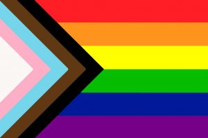 Inclusive pride flag: black and brown stripes representing people of color; pink, white, and blue stripes are a nod to the Trans Pride banner.