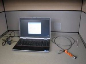 Laptop computer in a cubicle with cable and lock.