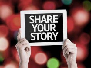 hands hold up sign with the words Share Your Story
