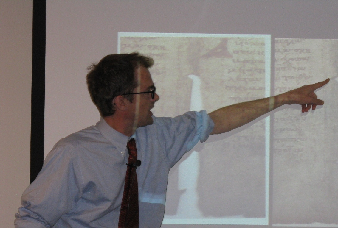 William Noel pointing to a presentation projection on a whiteboard.