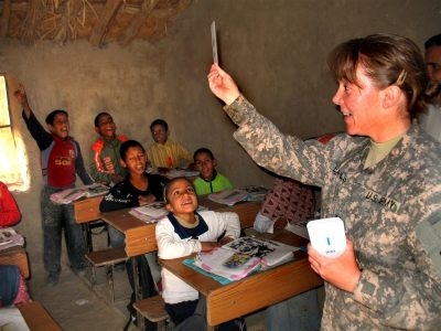 Army officer working with students in a school