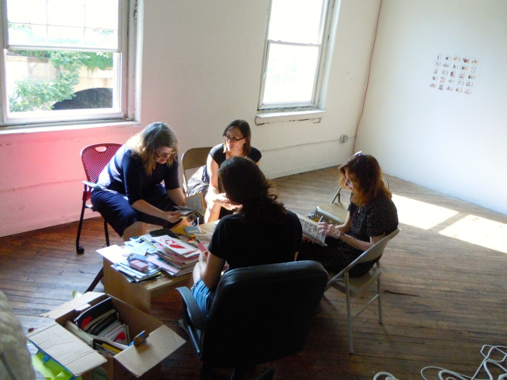 Librarians reviewing donor's zines.