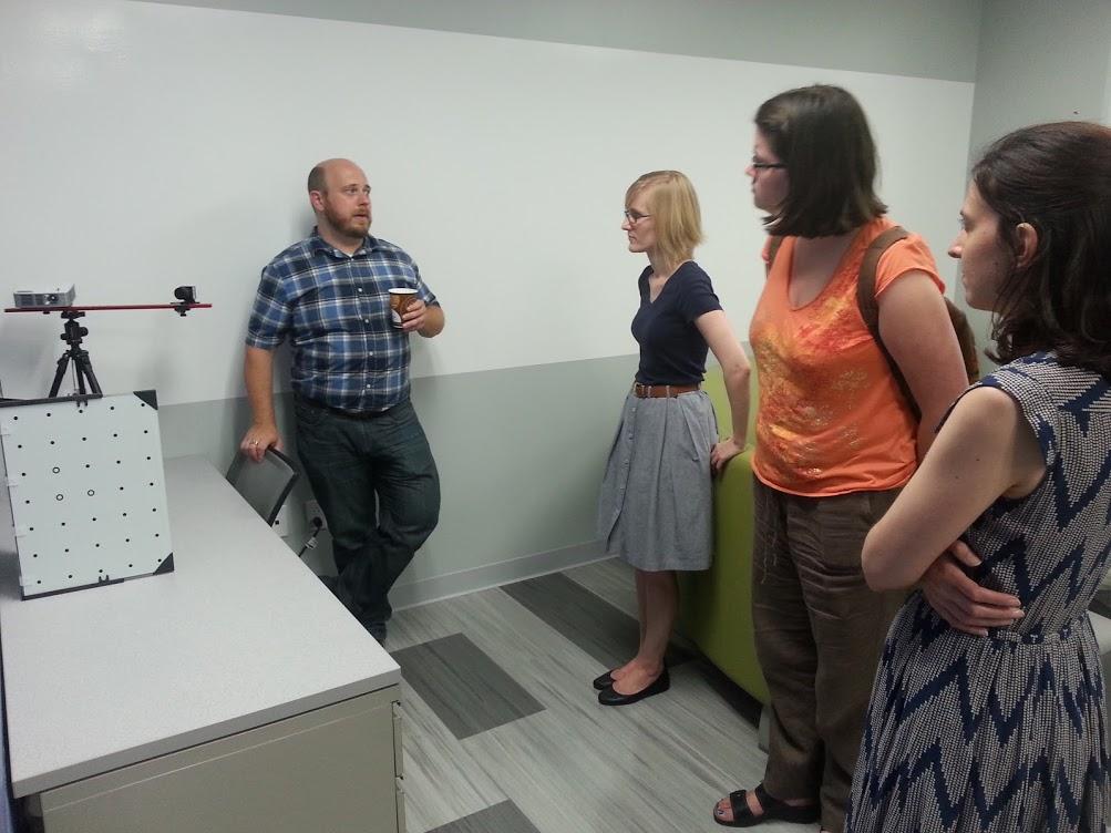 Matt Shoemaker speaking with two women near the 3D scanner