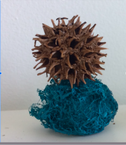 small sculpture - blue hardened wool with a sweetgum pod resting on top