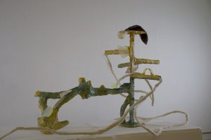 Green and Yellow undulating object holder. Small objects are placed on small platforms throughout sculptural holder